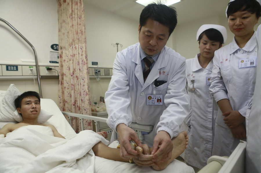 Handout photo of doctors checking on Xiao Wei's severed right hand attached to his ankle before the reattachment surgery at Xiangya Hospital in Changsha